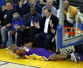 Los Angeles Lakers' Kobe Bryant ends up at the feet of Golden State Warriors' owner Joe Lacob and former player Jason Richardson in 1st quarter during NBA game at Oracle Arena in Oakland, Calif., on Tuesday, November 24, 2015.