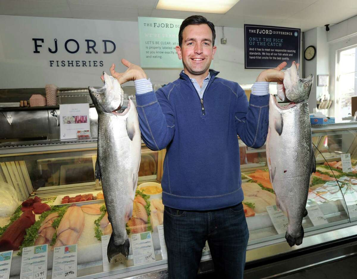 Jim Thistle, co-owner of the Fjord Fish Market, holds two farm-raised King Salmon from Marlborough Sound, New Zealand, at his Cos Cob store Tuesday.