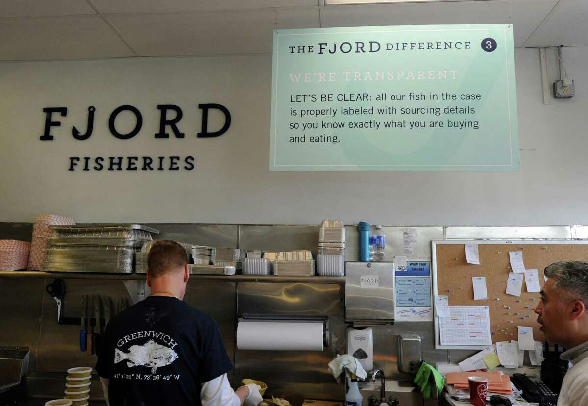 A transparency pledge sign regarding proper fish labeling and sourcing details hangs behind the counter at the Fjord Fish Market in the Cos Cob section of Greenwich, Conn., Tuesday, Nov. 24, 2015.