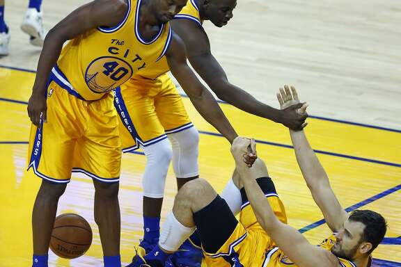 Golden State Warriors' Andrew Bogut is helped up by Harrison Barnes and Draymond Green in 3rd quarter against Los Angeles Lakers during NBA game at Oracle Arena in Oakland, Calif., on Tuesday, November 24, 2015.