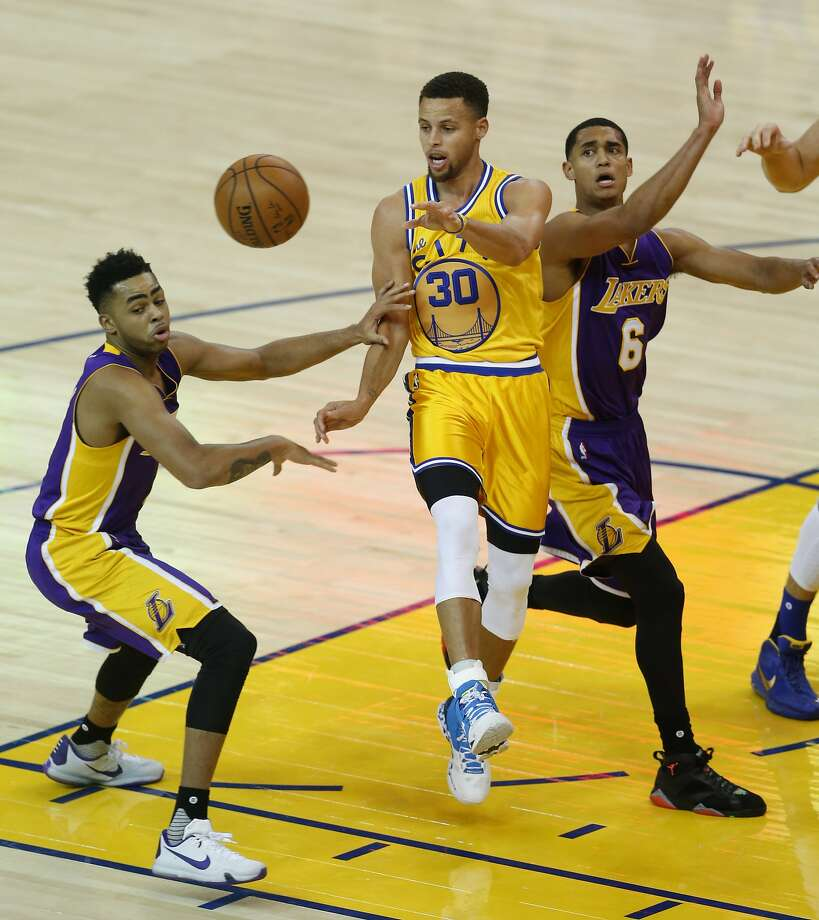 CAPTION CORRECTION- Golden State Warriors' Stephen Curry passes against Los Angeles Lakers' D'Angelo Russell and Jordan Clarkson (6) in 1st quarter during NBA game at Oracle Arena in Oakland, Calif., on Tuesday, November 24, 2015. Photo: Scott Strazzante, The Chronicle