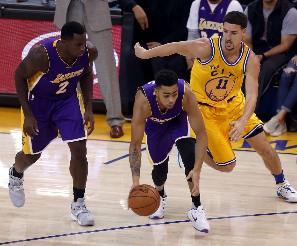 D'Angelo Russell dribbles the ball while being guarded by Klay Thompson during a game between the Warriors and the Los Angeles Lakers at Oracle Arena in Oakland, California, on Tuesday, Nov. 24, 2015.