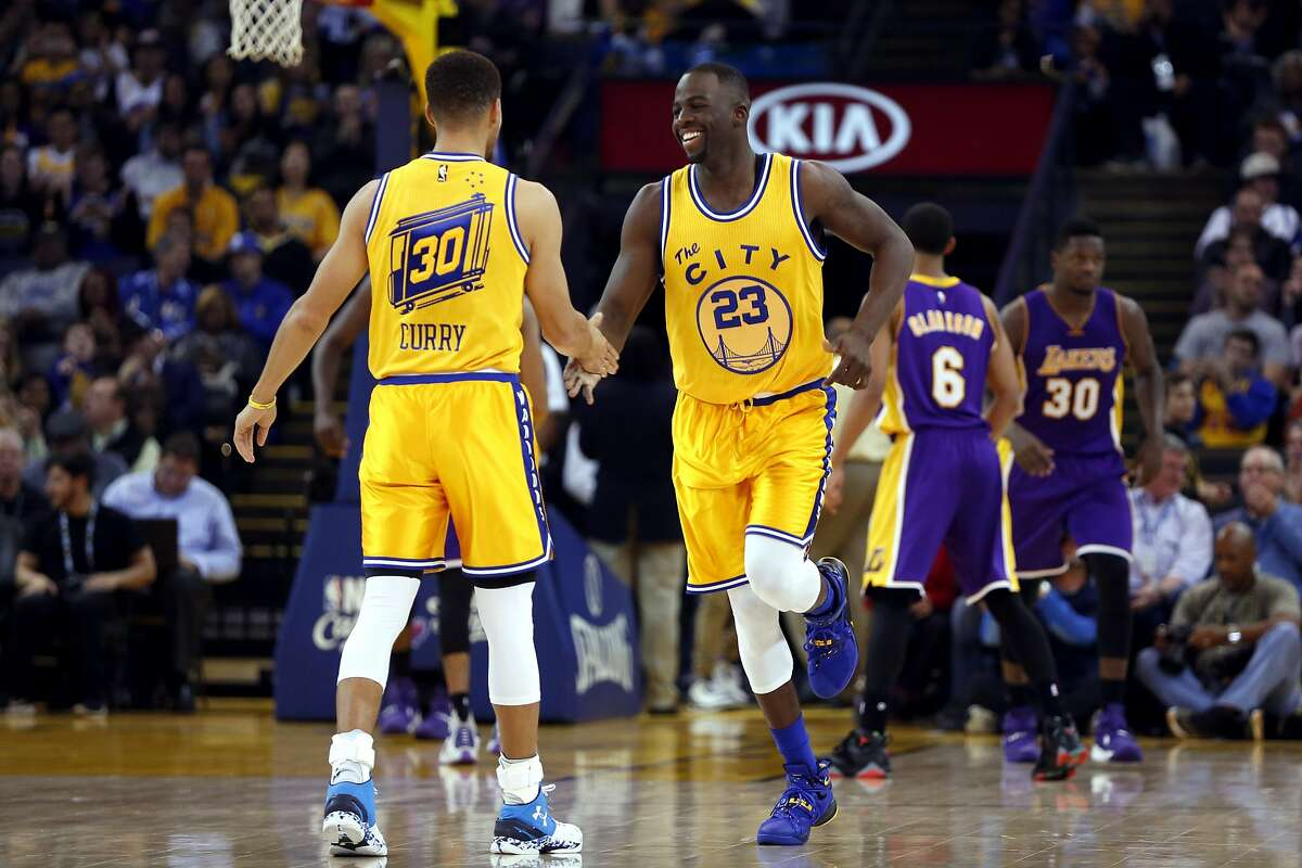 Draymond Green and Stephen Curry celebrate during a game between the Warriors and the Los Angeles Lakers at Oracle Arena in Oakland, California, on Tuesday, Nov. 24, 2015.