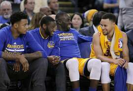 Stephen Curry (30), Draymond Green (23) Ian Clark (21) and Brandon Rush (4) laugh on the bench in the second half as the Golden State Warriors played the Los Angeles Lakers at Oracle Arena in Oakland, Calif., on Tuesday, November 24, 2015.