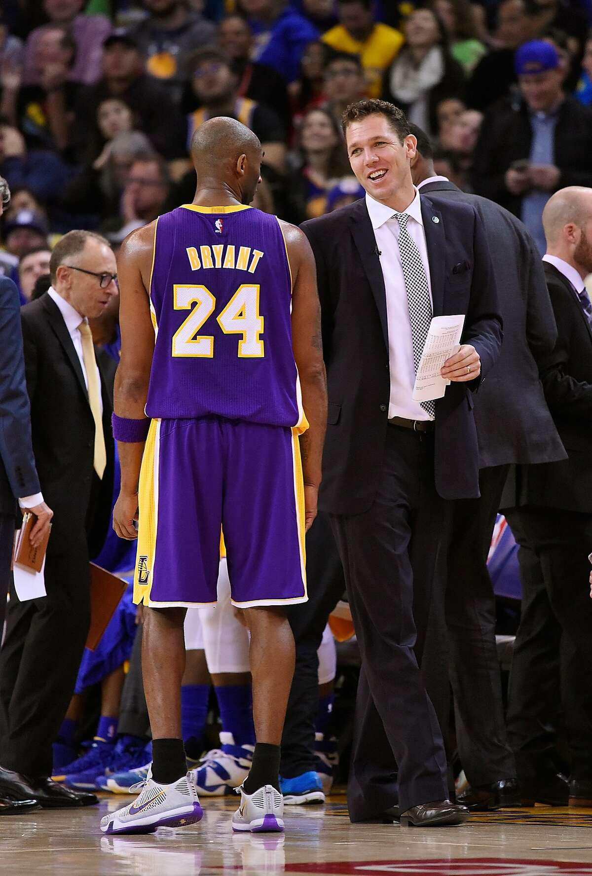 Kobe Bryant of the Los Angeles Lakers during a time out talks with interim head coach Luke Walton of the Golden State Warriors at ORACLE Arena on November 24, 2015 in Oakland, California.