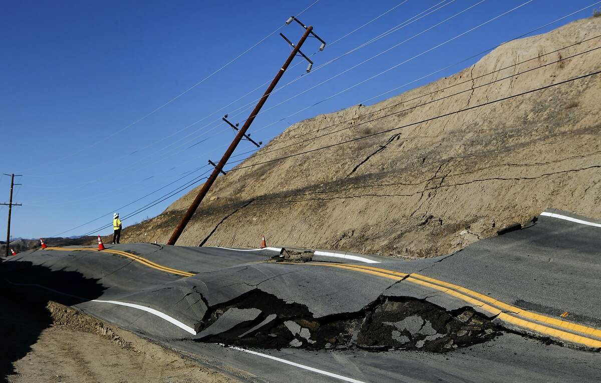 SANTA CLARITA, CA - NOVEMBER 20: A member of Los Angeles County Public Works surveys the damage to a telephone pole due to a landslide that also buckled Vasquez Canyon Road, between Lost Creek Road and Vasquez Way in Santa Clarita on November 20, 2015. (Mel Melcon/Los Angeles Times/Getty Images)
