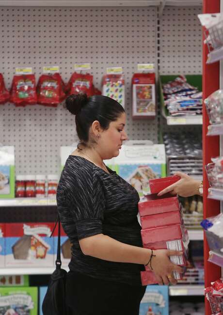 Laura Shatara (l to r) of San Francisco holds boxes of candy canes as Emily Sliwkowski adds one to the top as they shop for an office party in the trim a tree section at Target on Tuesday, November 24,  2015 in San Francisco, Calif. Photo: Lea Suzuki, The Chronicle