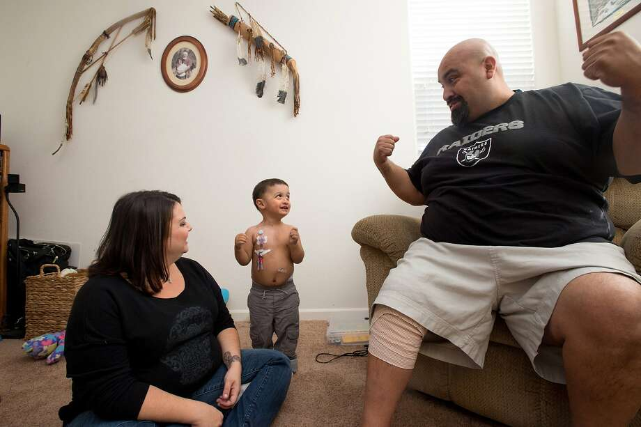 Xavier Pequeno (C) flexes for his parents Jessica Pequeno (L) and Higinio Pequeno III (R) at their home in Napa, California on November 19, 2015. Xavier's rare immune deficiency condition and Higinio's knee injury has made paying rent difficult for the family this holiday season. Photo: JOSH EDELSON / SAN FRANCISCO CHR