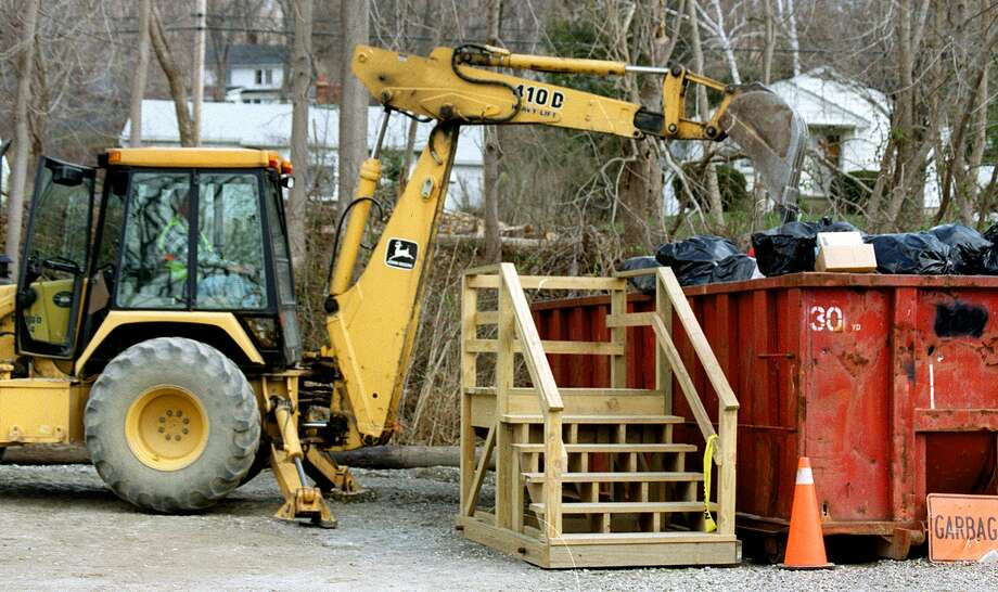 Backhoe dumps items for recycling at New Milford Recycling Center. A subcommittee report this November recommends keeping the center town-run. Photo: File Photo / File Photo / The News-Times File Photo