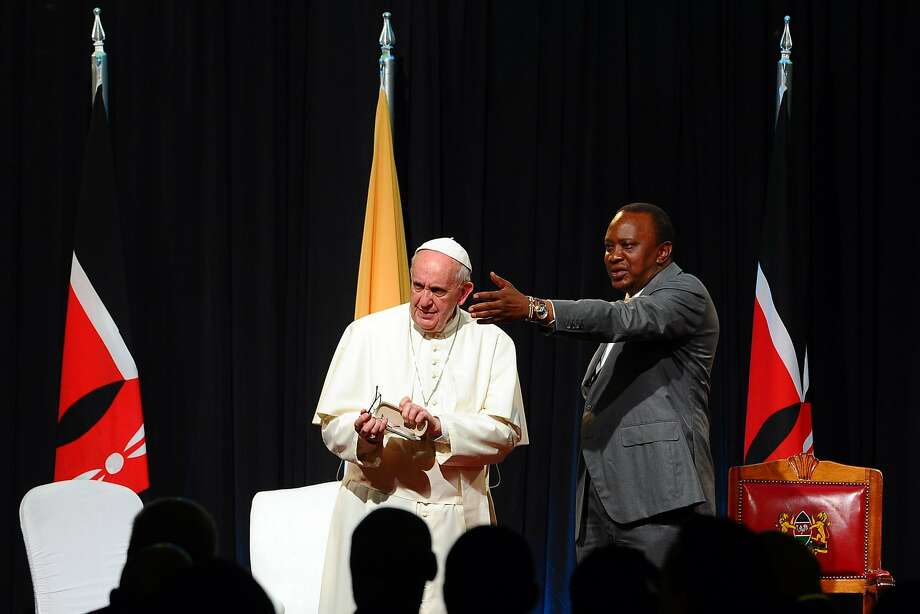 """Kenyan President Uhuru Kenyatta (R) gestures next to Pope Francis at the State House of Nairobi on November 25, 2015. Pope Francis said the world was facing a """"grave environmental crisis"""" as he arrived in Kenya on Wednesday on a landmark Africa trip just days before a crucial UN summit aimed at curbing climate change. He also warned of the need to tackle poverty as a key driver of conflict and violence as he kicked off a landmark Africa trip fraught with security concerns and urged Kenya's leaders to work with """"transparency"""" to ensure a fair distribution of national resources as criticism grows over runaway graft in this east African country. AFP PHOTO / JOHN MUCHUCHAJohn Muchucha/AFP/Getty Images Photo: John Muchucha, AFP / Getty Images"""