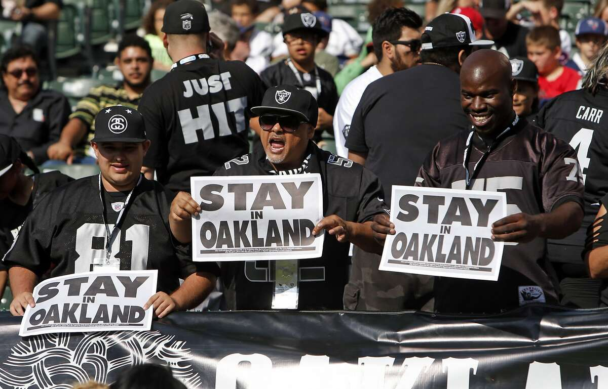 """Oakland Raiders' fans show """"Stay in Oakland"""" signs before Raiders play Arizona Cardinals in preseason game at O.co Coliseum in Oakland, Calif., on Sunday, Aug. 30, 2015."""