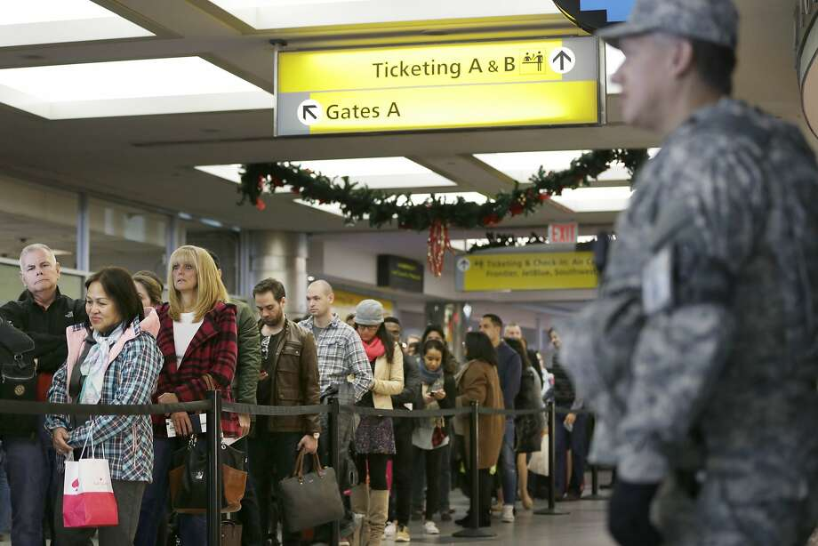 Passengers wait to pass through airline security at LaGuardia Airport in New York. An estimated 47 million Americans are expected to travel at least 50 miles from home. Photo: Seth Wenig, Associated Press