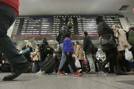 Amtrak passengers walk to their gates in New York's Pennsylvania Station, Wednesday, Nov. 25, 2015. An estimated 46.9 million Americans are expected to take a car, plane, bus or train at least 50 miles from home over the long holiday weekend, according to the motoring organization AAA. (AP Photo/Richard Drew)