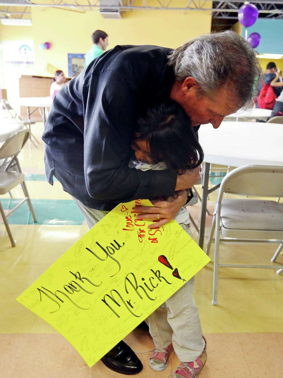 Rick Cavender (left) hugs Kayla Segovia, 6, after performing with The Rick Cavender Band during a free Rock 'N Roll Pizza Party April 6, 2015, at SA Youth's Dan Cook Youth Center.