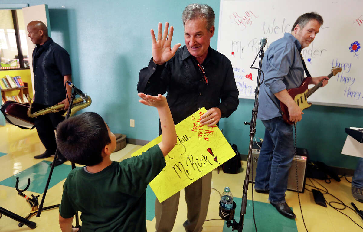 Rick Cavender (center) high-fives Noe Martinez , 9, after performing with The Rick Cavender Band at a free Rock 'N Roll Pizza Party, as band members Billy Ray Sheppard (rear left) and Keith Harter (right) pack, April 6, 2015 at SA Youth's Dan Cook Youth Center.