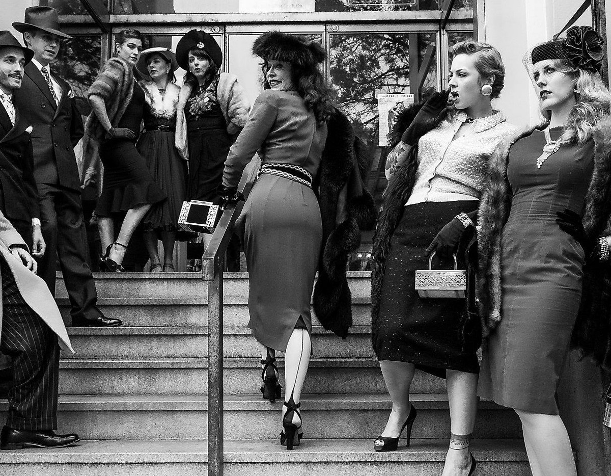 Decades of Fashion owner Cicely Hansen (second from right) climbing the stairs of her store on Haight Street in a 1940s ensemble from her personal collection.