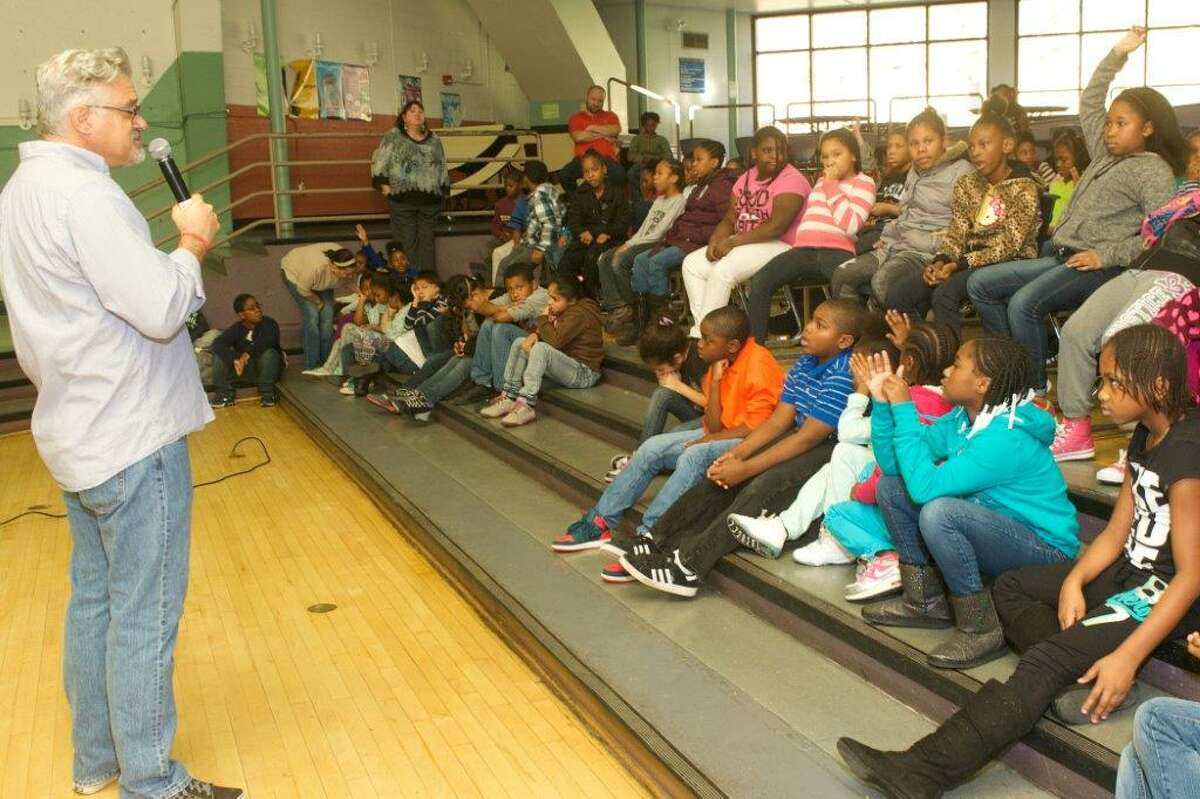 """Michael Fry, author of """"The Odd Squad"""" middle grade series of illustrated novels, answers questions from students at Arbor Hill Elementary School. Fry received the 10th annual Denise McCoy Legacy Award on Nov. 20. (Joann Hoose Photography)"""