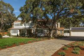 Mature trees shade a front yard with level lawn and drought-tolerant plantings on opposite sides of the brick driveway.