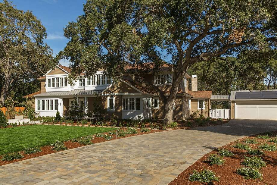 Mature trees shade a front yard with level lawn and drought-tolerant plantings on opposite sides of the brick driveway. Photo: Scott Dubose