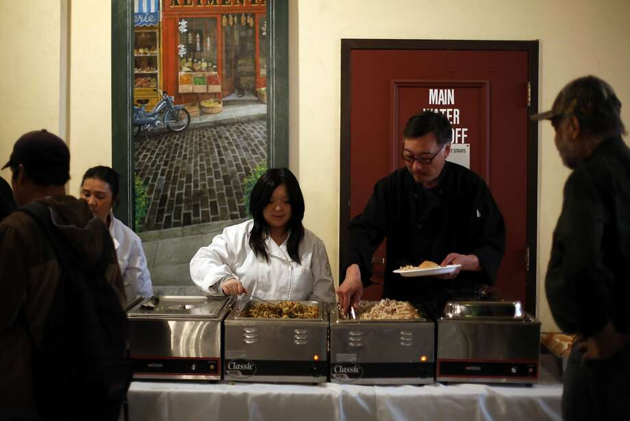 Karen Low (center) and Kenry Kwong serve Thanks giving dinner fo r the SRO residents of the Cadillac Hotel in S.F.'s Tenderloin. Photo: Connor Radnovich, The Chronicle