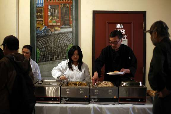 Karen Low (left) and Kenry Kwong serve food during a Thanksgiving dinner at Cadillac Hotel in San Francisco, California, on Wednesday, Nov. 25, 2015.