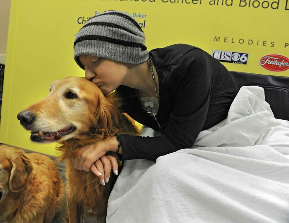 Reese Johnson, 14, of Ballston Spa gives therapy dog Riley a kiss at The Melodies Center in Albany Medical Center on Wednesday, Nov. 25, 2015 in Albany, N.Y.  (Lori Van Buren / Times Union) Photo: Lori Van Buren / 10034433A