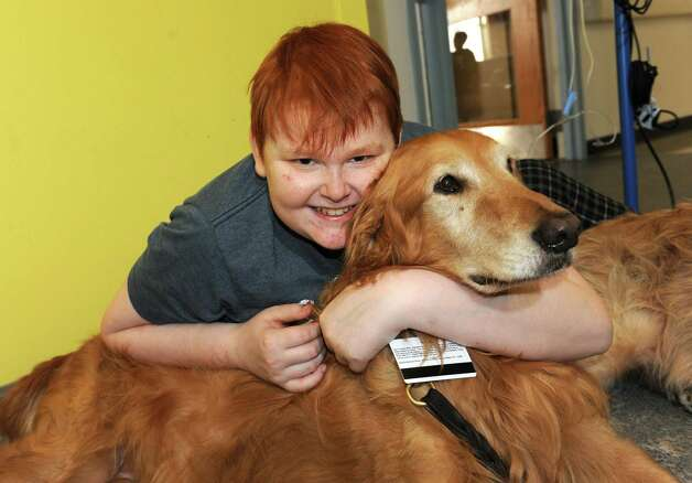 Jeffery Jackson, 13, of Queensbury hugs therapy dog Mac at The Melodies Center in Albany Medical Center on Wednesday, Nov. 25, 2015 in Albany, N.Y.  (Lori Van Buren / Times Union) Photo: Lori Van Buren / 10034433A
