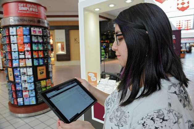 Guest services representative Shirley Robalino holds an iPad she uses as part of the concierge service offered at Wilton Mall on Friday, Nov. 20, 2015 in Schenectady, N.Y. Shoppers can text the concierge service for assistance to finding stores and other things. (Lori Van Buren / Times Union) Photo: Lori Van Buren / 10034391A