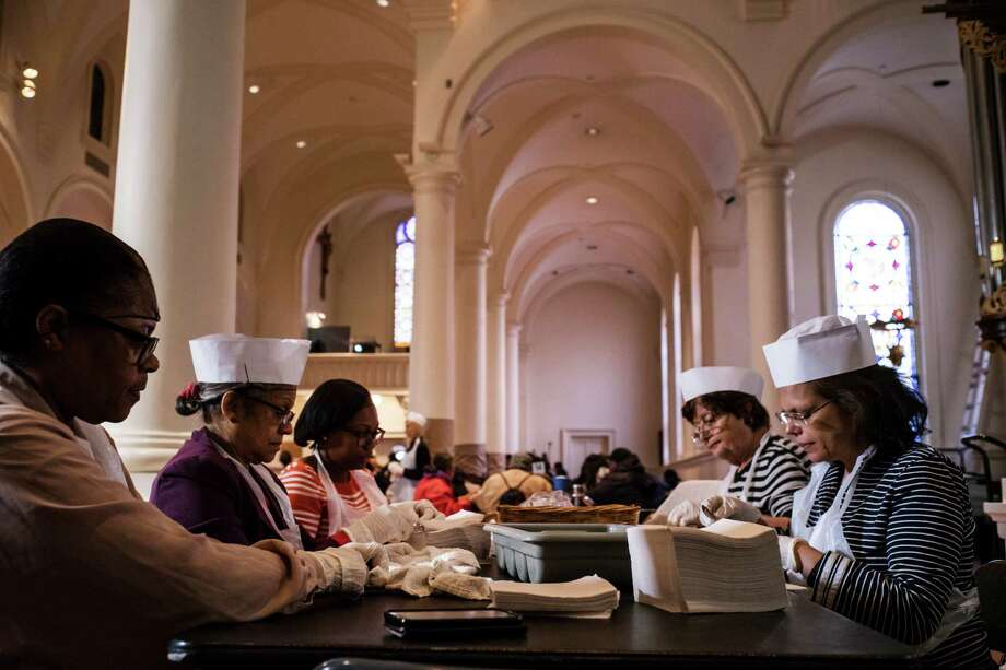 STANDALONE — Volunteers fold utensils in napkins for upcoming meals at the Church of the Holy Apostles in New York, Nov 25. 2015. The church hosts one of the busiest soup kitchens in the city, serving 1,200 people a day, five days a week. (Todd Heisler/The New York Times) ORG XMIT: XNYT122 Photo: TODD HEISLER / NYTNS