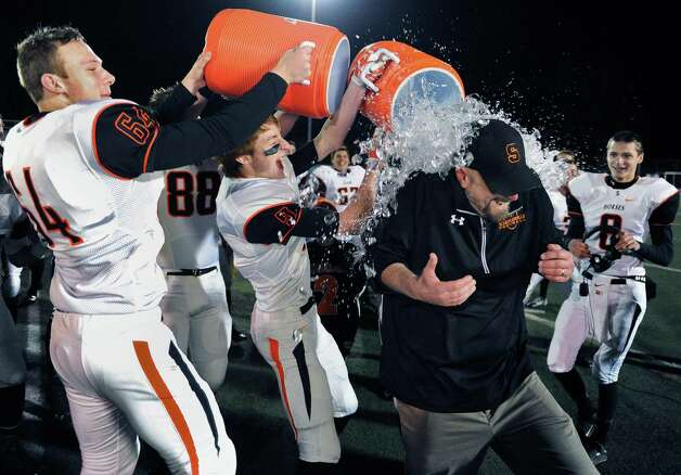 Schuylerville's Tom Cappelletti, left, and Zach Pierce douse coach John Bowen after their win over Westlake in the Class B semifinal game Saturday Nov. 21, 2015 in Kingston, NY.  (John Carl D'Annibale / Times Union) Photo: John Carl D'Annibale / 10034363A