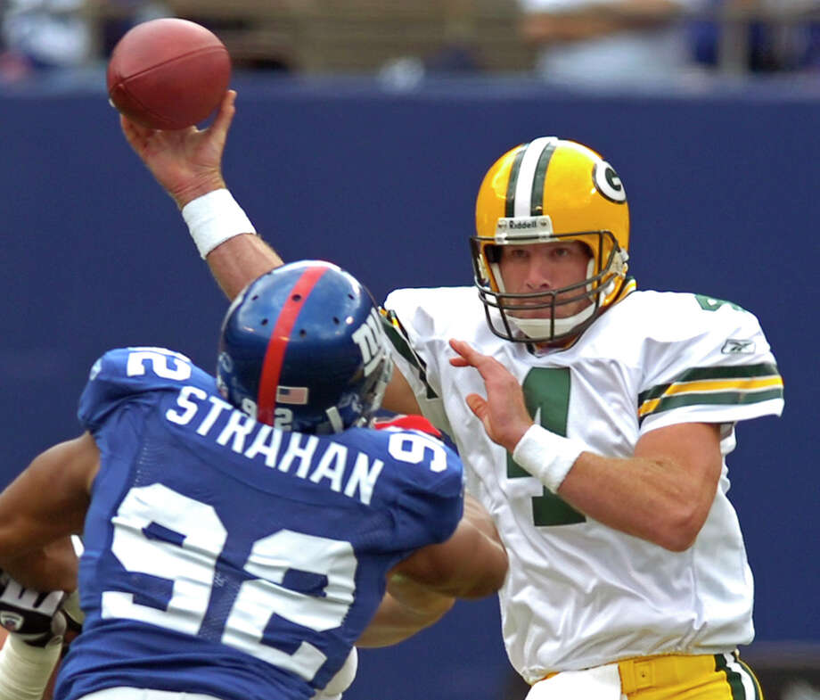 FILE - In this Sept. 16, 2007 file photo, Green Bay Packers quarterback Brett Favre, right, passes the ball as he is pressured by New York Giants defensive end Michael Strahan (92) during first quarter NFL football at Giants Stadium in East Rutherford, N.J. Packers quarterback Aaron Rodgers is looking forward to the return of predecessor Brett Favre on Thanksgiving night, Thursday, Nov. 26, 2015 at Lambeau Field. Favre's name and retired number will be unveiled on the north facade of the stadium at halftime of Green Bay's game against the Chicago Bears.  (AP Photo/Bill Kostroun, File) ORG XMIT: NY166 Photo: Bill Kostroun / AP