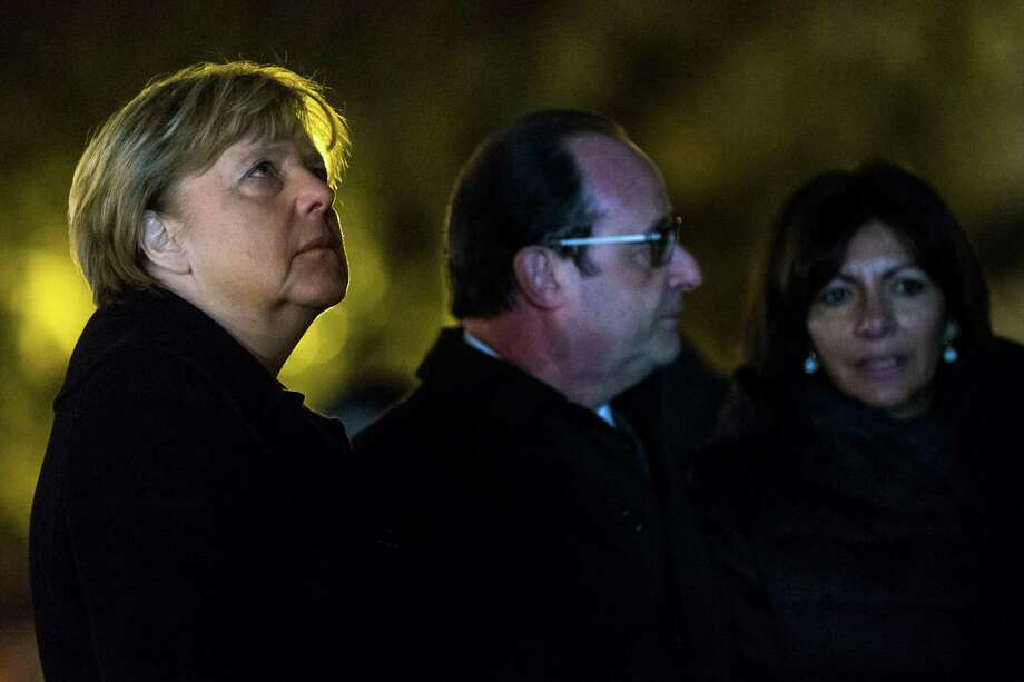 From left, German Chancellor Angela Merkel, French president Francois Hollande and Paris Mayor Anne Hidalgo pay their respects to the victims of the attacks of the 13th November on the Place de la Republique prior to a meeting at the Elysee Palace, in Paris, Wednesday, Nov. 25, 2015. Merkel's visit to Paris is part of president Hollande's diplomatic offensive to get the international community to bolster the campaign against the Islamic State militants. (Etienne Laurent, Pool Photo via AP) ORG XMIT: XPAR107 Photo: (Etienne Laurent / EPA POOL