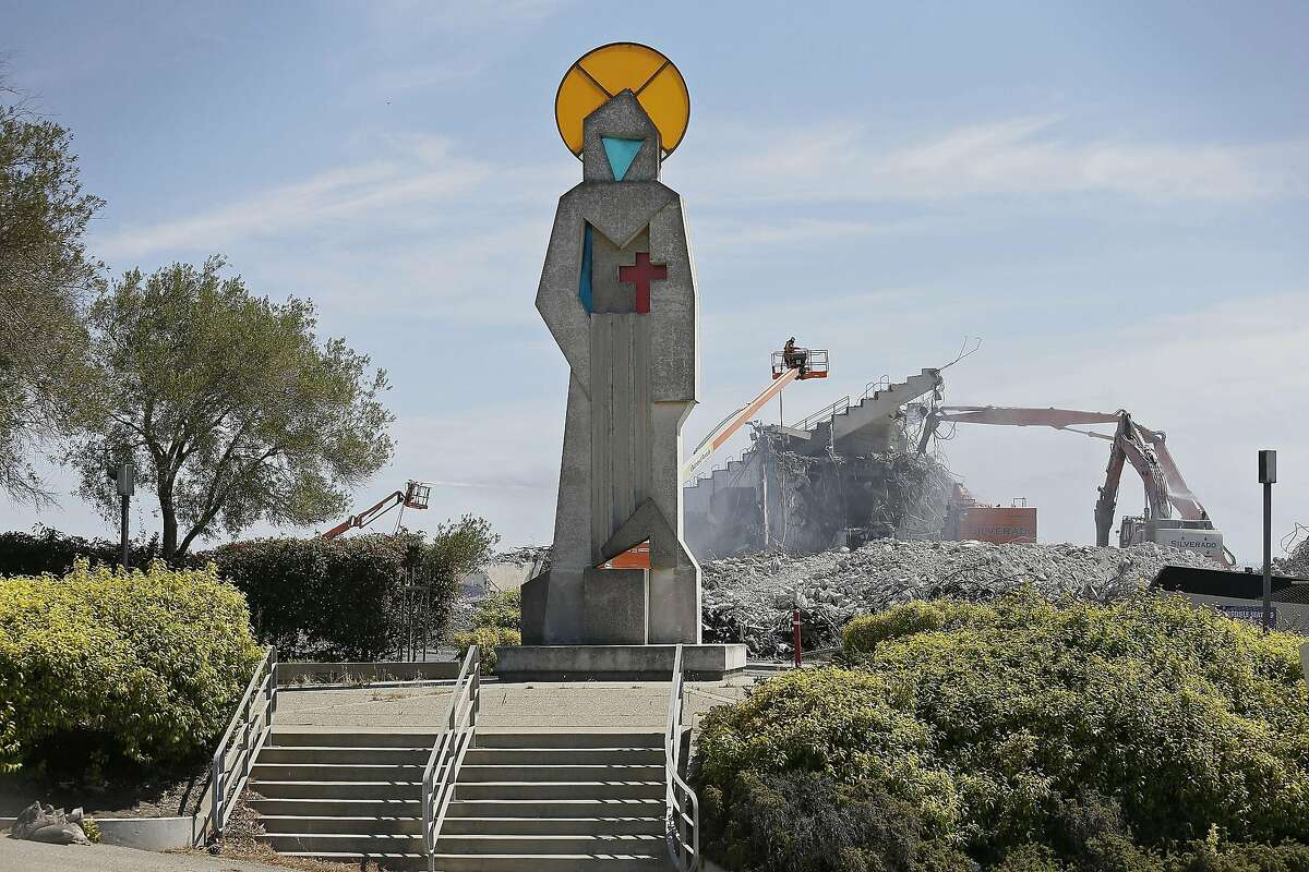 An abstract sculpture representing St. Francis, the patron saint of San Francisco, and a small section of seating still stand as demolition continues at Candlestick Park Tuesday, June 30, 2015, in San Francisco. The storied park is being torn down so houses, a hotel and a shopping center can be built on the site of the former home of the San Francisco Giants baseball team and 49ers football team. The park opened more than 50 years ago and was known for its chilly conditions brought by whipping winds and fog from San Francisco Bay. The sculpture, done by Ruth Wakefield Cravath, will be put into storage as city officials seek a new home for it. (AP Photo/Eric Risberg)