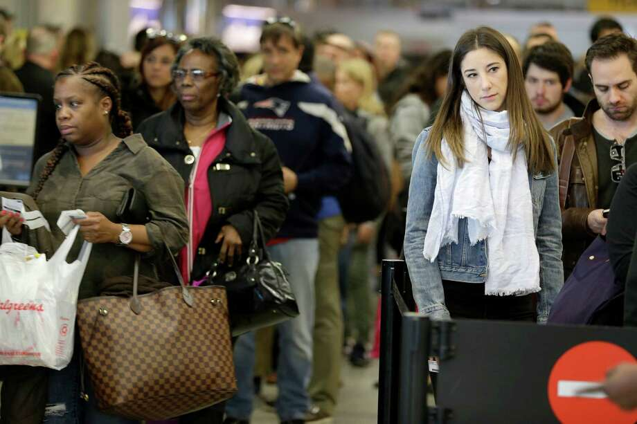 Passengers wait in line to clear security at LaGuardia Airport in New York, Wednesday, Nov. 25, 2015. An expanded version of America's annual Thanksgiving travel saga was under way Wednesday with gas prices low and terrorism fears high. An estimated 46.9 million Americans are expected to take a car, plane, bus or train at least 50 miles from home over the long holiday weekend, according to the motoring organization AAA. That would be an increase of more than 300,000 people over last year, and the most travelers since 2007. (AP Photo/Seth Wenig) ORG XMIT: NYSW110 Photo: Seth Wenig / AP