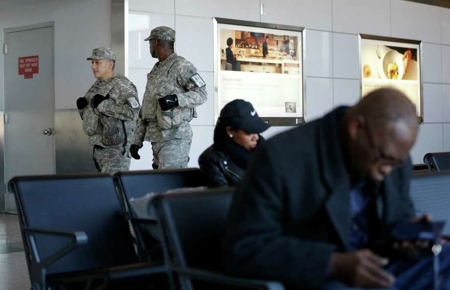 Security personnel walk round a terminal at LaGuardia Airport in New York, Wednesday, Nov. 25, 2015. An expanded version of America's annual Thanksgiving travel saga was under way Wednesday with gas prices low and terrorism fears high. An estimated 46.9 million Americans are expected to take a car, plane, bus or train at least 50 miles from home over the long holiday weekend, according to the motoring organization AAA. That would be an increase of more than 300,000 people over last year, and the most travelers since 2007. (AP Photo/Seth Wenig) ORG XMIT: NYSW102 Photo: Seth Wenig / AP