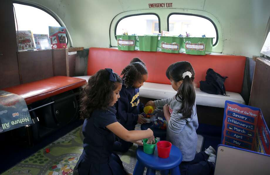 Valentina Morales (left), Mariah Andrews and Yaretzi Prado play inside a preschool operating out of an old bus at Aspire Schools' Monarch Academy in East Oakland, where demand for preschool is heavy and supply is light. Photo: Paul Chinn, The Chronicle