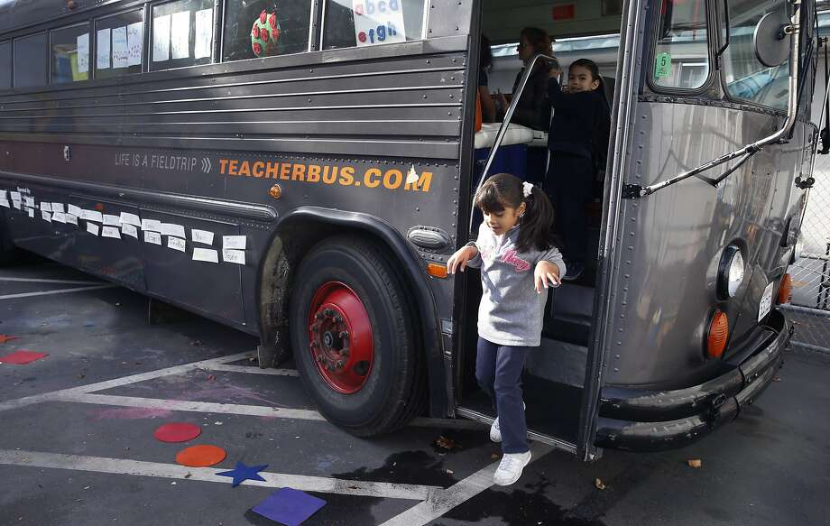 Yaretzi Prado, 4, hops out of an old bus serving as a preschool classroom at the Aspire Monarch Academy school in Oakland, Calif. on Wednesday, Nov. 18, 2015. Photo: Paul Chinn, The Chronicle