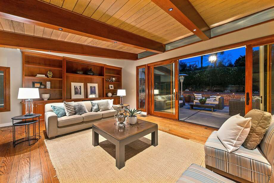 Wood-framed sliding doors open to a patio off the home's additional wing. Photo: OpenHomesPhotography.com