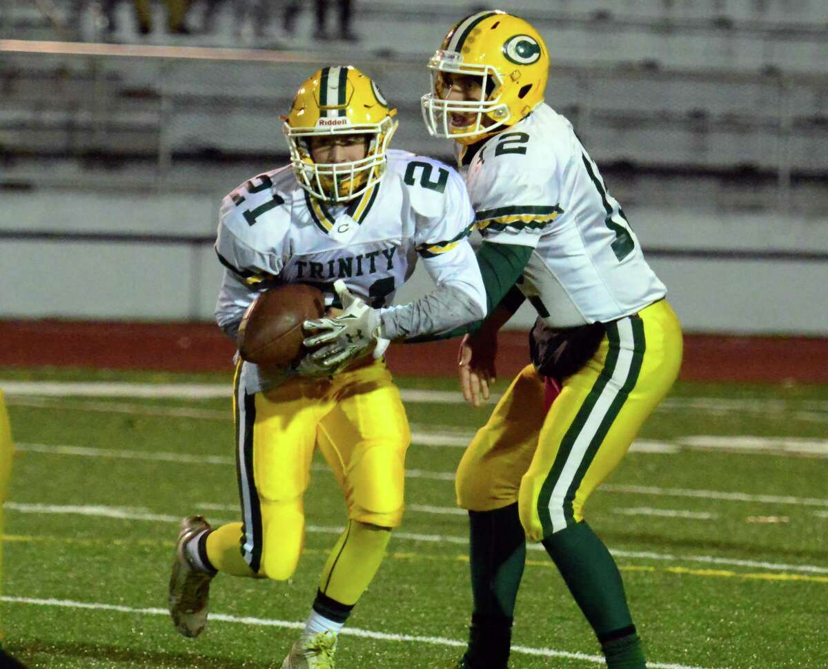 Running back Nick Meilia takes the hand off from Anthony Lombardi. High school football action between Trinity Catholic and Central in Bridgeport, Conn. on Friday Nov. 13, 2015.