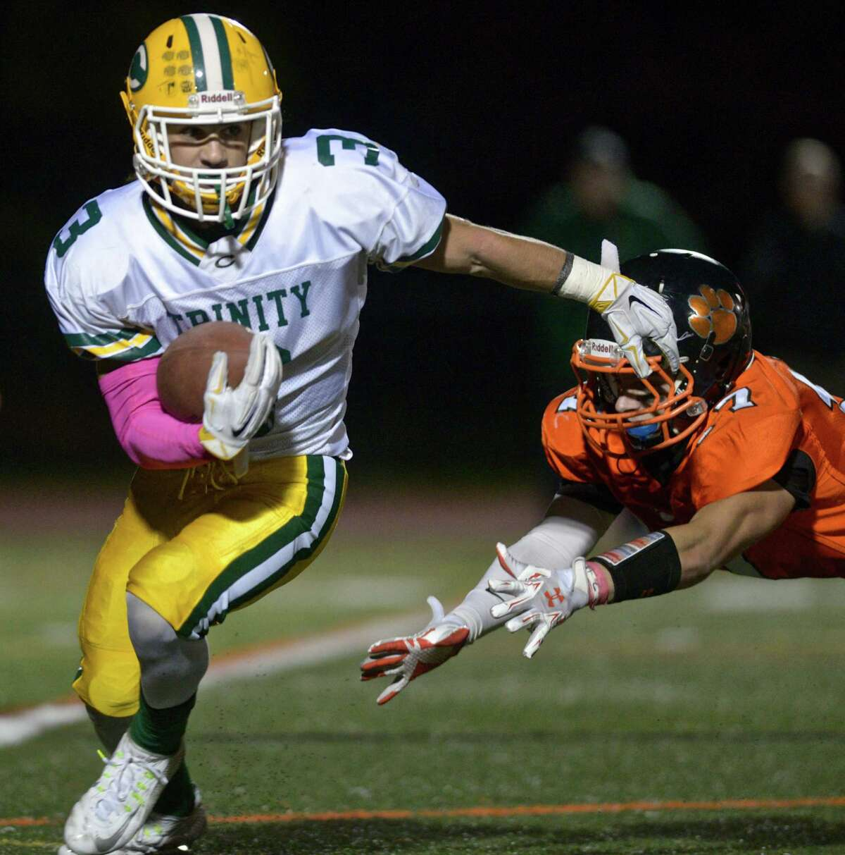 Trinity's Jonmichael Bivona (3) stays out of the reach of Ridgefield's William Carpenter (7) in the football game between Trinity Catholic and Ridgefield high schools, on Friday night, October 16, 2015, played at Ridgefield High School, Ridgefield, Conn.