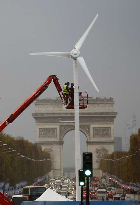 Employees install a wind turbine in Paris in preparation of the Conference on Climate Change COP21. Photo: Chesnot, Getty Images