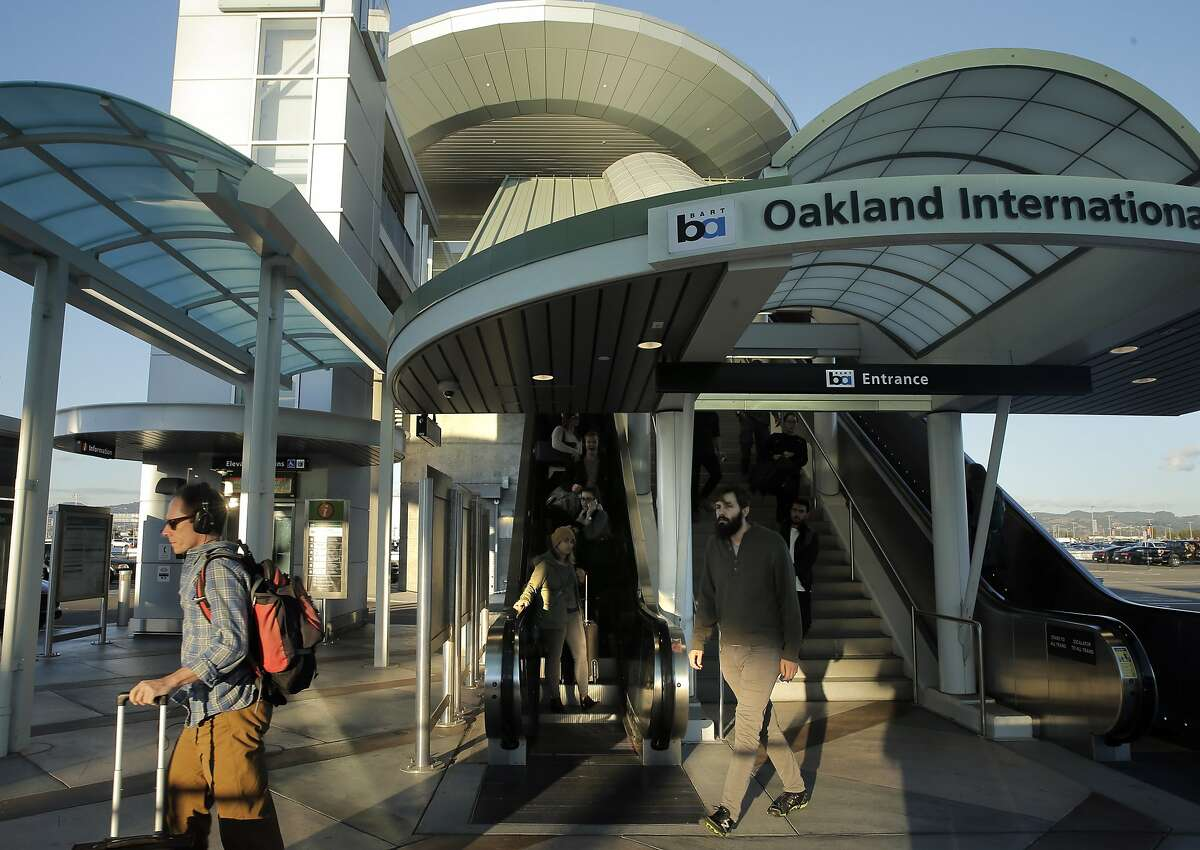 Airport passengers arrive at Oakland International Airport from the Oakland Airport Connector from the Coliseum BART Station in Oakland, Calif., on Wednesday, November 25, 2015.