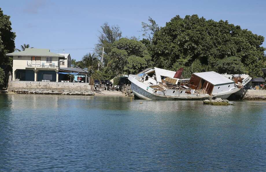 A boat lies wrecked and stuck on a sea wall on Majuro Atoll in the Marshall Islands after a king tide caused massive flooding and damaging many sea craft. Photo: Rob Griffith, Associated Press
