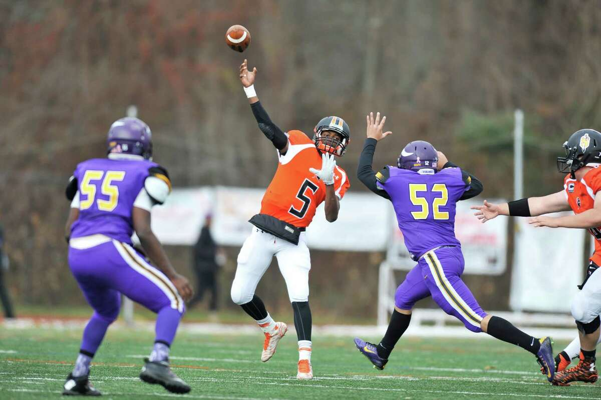 Stamford quarterback Troy Duncan launches a throw while under pressure.
