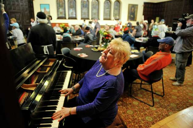 Albany County Legislator and volunteer Mary Lou Connolly sings and plays the piano for guests at the annual Equinox Thanksgiving Day Community Dinner at First Presbyterian Church on Thursday, Nov. 26, 2015, in Albany, N.Y.  Connolly has been playing the piano at the event for over 13 years.  (Paul Buckowski / Times Union) Photo: PAUL BUCKOWSKI / 10034447A