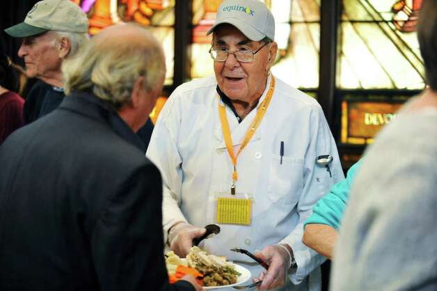 Volunteer chef Norm Shapiro talks with a guest as he dished out turkey at the annual Equinox Thanksgiving Day Community Dinner at First Presbyterian Church on Thursday, Nov. 26, 2015, in Albany, N.Y.  (Paul Buckowski / Times Union) Photo: PAUL BUCKOWSKI / 10034447A