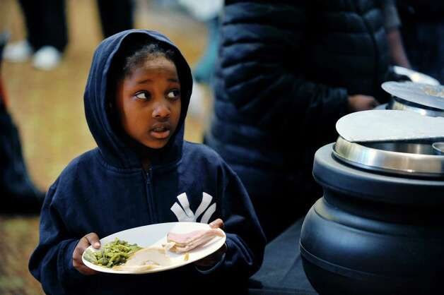 Selena mackey, 6, of Albany makes her way through the food line at the annual Equinox Thanksgiving Day Community Dinner at First Presbyterian Church on Thursday, Nov. 26, 2015, in Albany, N.Y.  (Paul Buckowski / Times Union) Photo: PAUL BUCKOWSKI / 10034447A
