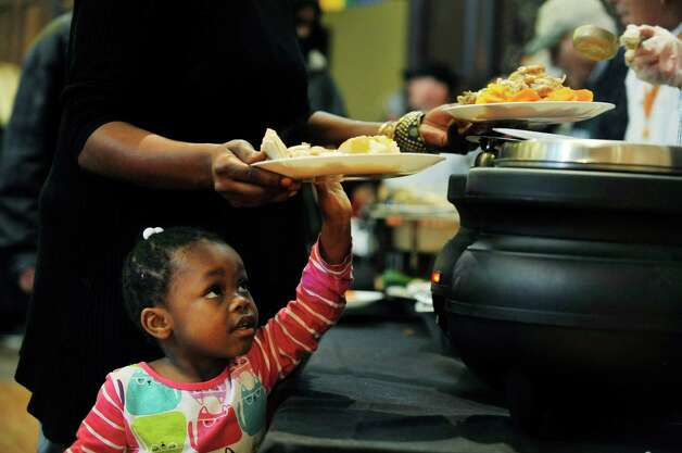 Syneigha Terrell, 2, of Rensselaer helps her mother, Rachel Burden hold up her plate to get gravy on it at the annual Equinox Thanksgiving Day Community Dinner at First Presbyterian Church on Thursday, Nov. 26, 2015, in Albany, N.Y.  (Paul Buckowski / Times Union) Photo: PAUL BUCKOWSKI / 10034447A
