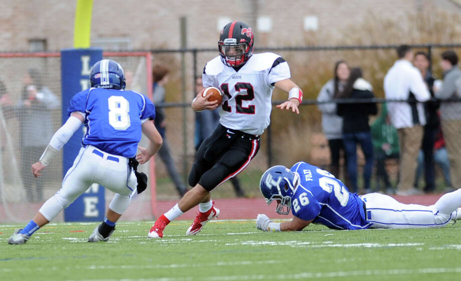 Fairfield Warde's Jack Potenza carries the ball past Fairfield Ludlowe defenders Josh Evans, left, and Spencer Foley during the annual Thanksgiving Day football game Thursday, Nov. 26, 2015, at Ludlowe. Photo: Autumn Driscoll / Hearst Connecticut Media / Connecticut Post