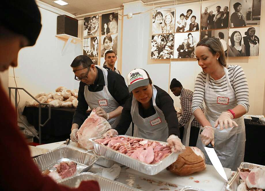 Volunteers John Lee (left), Catherine Chao Thomsen (middle) and Sarah Potter (right) carve ham at Freedom Hall for the Glide Memorial Thanksgiving feast in San Francisco, California, on Thursday, November 26, 2015. Volunteers carved 400 turkeys and 120 ham today for the Glide Memorial thanksgiving feast. Photo: Liz Hafalia, The Chronicle